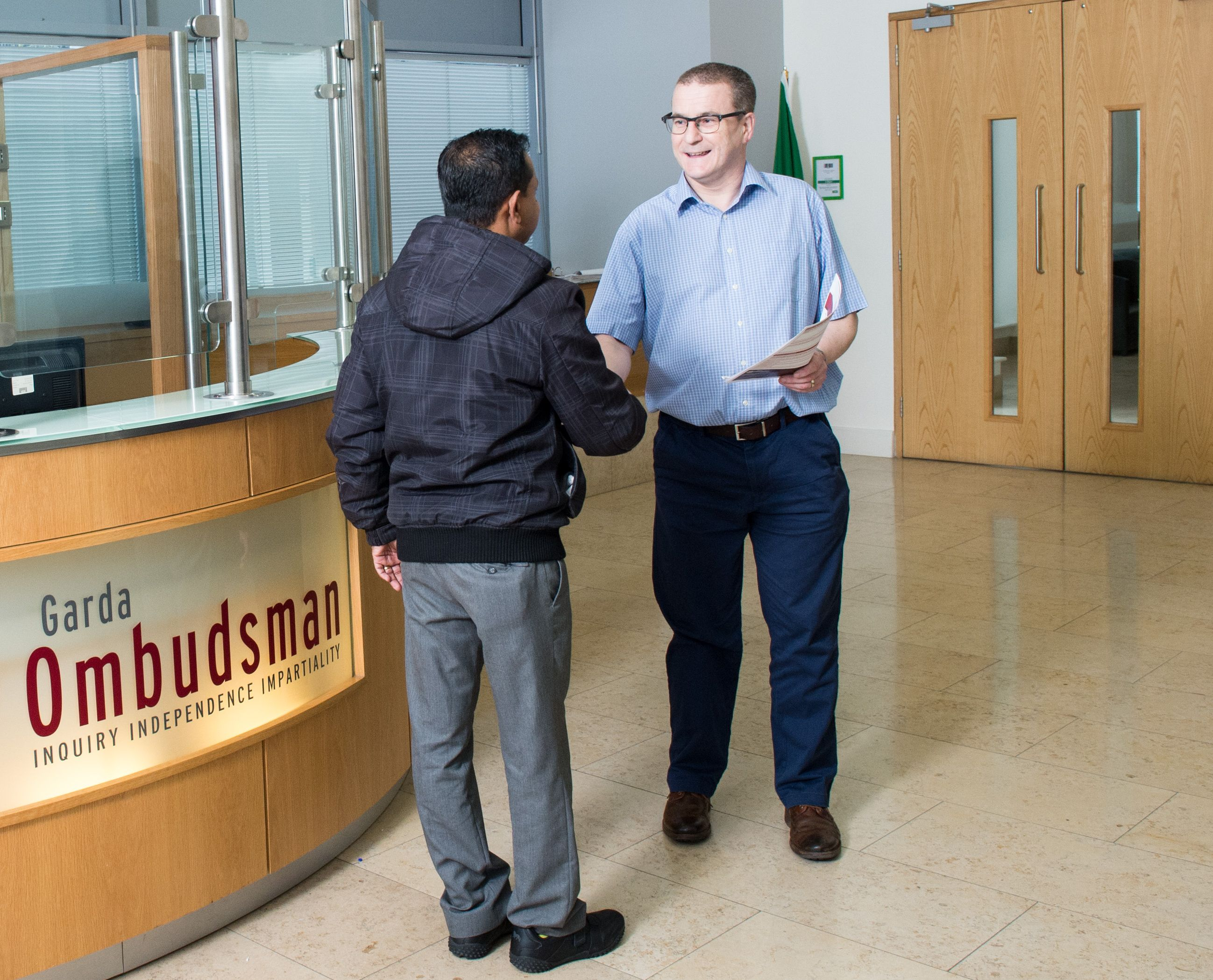 Man being welcomed by a Garda Ombudsman member of staff
